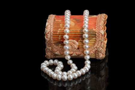 Jewelery box with necklaces on black  background photo