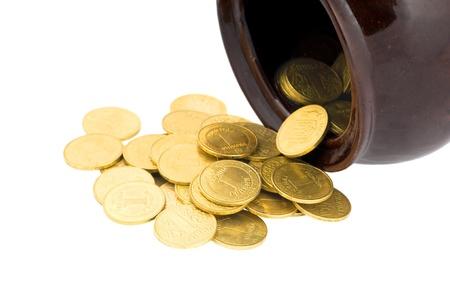 Ceramic pot with metallic money of the yellow metal on a white background photo
