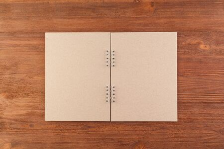 Open notebook in dark paper on a wooden table. Top view and horizontal orientation.
