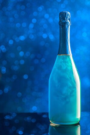 A bottle of blue-colored champagne against the background of sparkling lights. Template for design. Copy space and vertical orientation Stockfoto