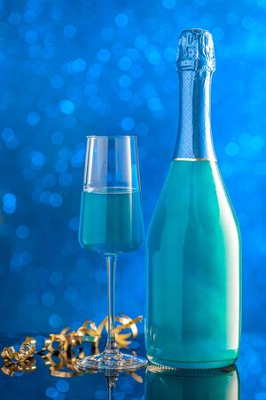 A bottle and a glass of blue-colored champagne against the background of sparkling lights. Template for design. Copy space and vertical orientation.