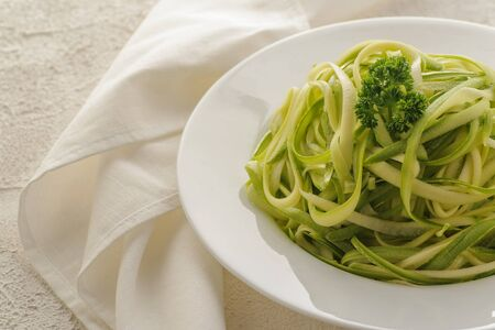 Zucchini spaghetti. Healthy natural food for the diet. Low in calories. Large portion on a white plate with cherry tomatoes and olive oil. Close up and horizontal orientation. Copy space.