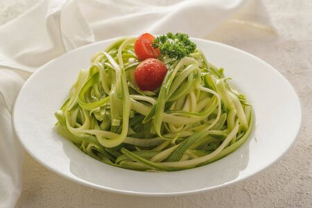 Zucchini spaghetti. Healthy natural food for the diet. Low in calories. Large portion on a white plate with cherry tomatoes and olive oil. Close up and horizontal orientation.