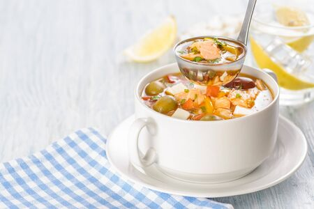 Fish soup with salmon and vegetables. A large portion of the soup is served on a white dish. Close up and horizontal orientation.