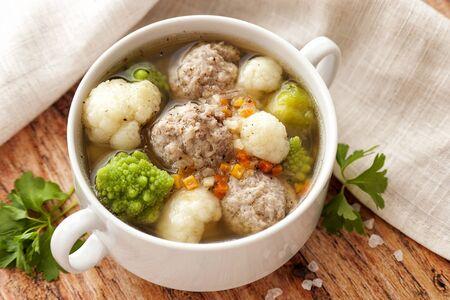 Heiße dicke Suppe mit Fleischbällchen und Kohlmischung. Eine große Portion wird auf einem weißen Teller serviert. Fertig für den Verzehr. Nahaufnahme und horizontale Ausrichtung.