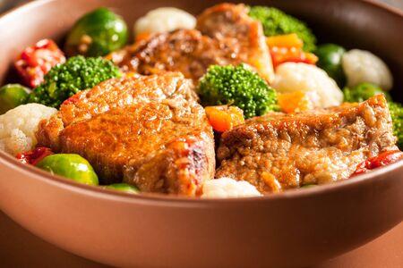 Spezzatino di carne con verdure in salsa densa. Una porzione abbondante in un piatto fondo è pronta da mangiare. Stile rustico e arredamento in legno. Primo piano e orientamento orizzontale.