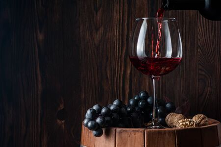 Old red wine. Traditional production and storage of wine. Wine is poured into a glass from a bottle. Copy space. Close up and horizontal orientation.