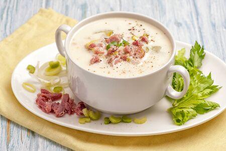 Zuppa cremosa con pancetta e verdure. Una grande porzione di zuppa in una ciotola bianca profonda. Pronto a mangiare. Primo piano e orientamento orizzontale.