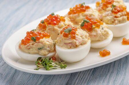 Uova ripiene con caviale rosso. Spuntino russo festivo tradizionale. Una grande porzione viene servita su un piatto bianco. Primo piano e orientamento orizzontale.