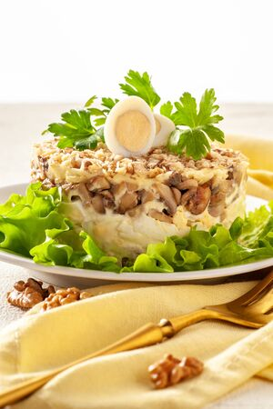 Chicken Salad. Multilayer salad with chicken, mushrooms and eggs and walnut. Portion served on a plate and ready to eat. Close up and vertical orientation.