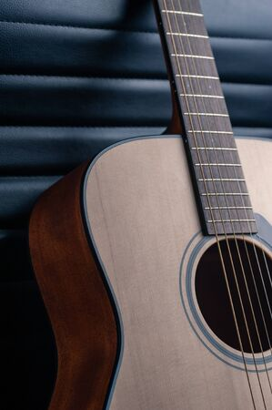Beautiful guitar on a textured leather background. Close-up image of a musical instrument. Selective focus. Vertical orientation.