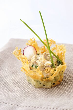 Portioned snack in baked crispy cheese tartlet. Close up and vertical view.