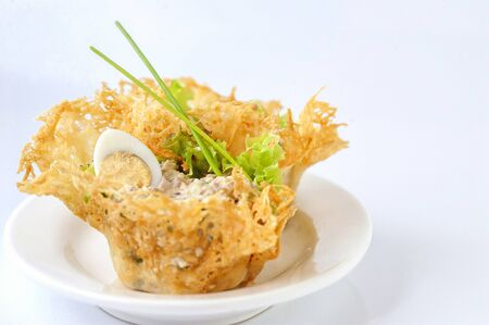 Portioned snack in baked crispy cheese tartlet. Close up and horizontal view.