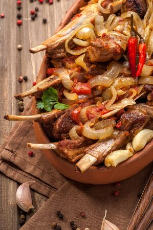 Fried lamb chops with fried onions, garlic and fresh herbs. A large portion is served on a clay plate and decorated in a rustic style. Close up and vertical orientation. Reklamní fotografie