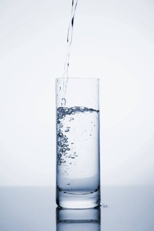 Clear mineral water is poured into a glass with ice. Fluid in motion. Copy space. Close up and vertical orientation. Фото со стока
