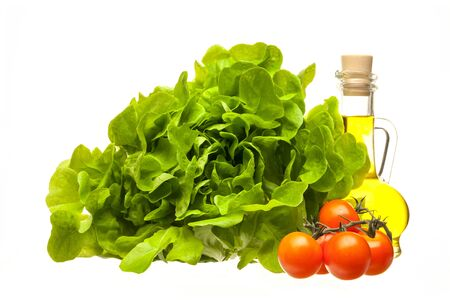 Fresh lettuce leaves, olive oil and cherry tomatoes isolated on a white background. The concept of diet, vegetarian and healthy eating. Close-up.