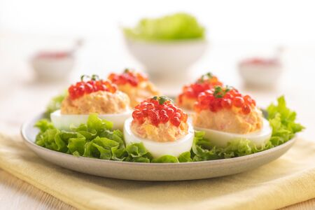 Stuffed eggs with red caviar. Traditional festive Russian snack. A large portion is served on a white plate. Close-up.