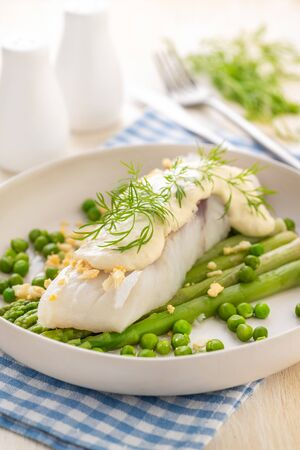 Steamed white fish fillet with asparagus and green peas and thick sauce. A large portion is served on a white plate and served with hollandaise sauce. Ready to eat. Close-up. Archivio Fotografico