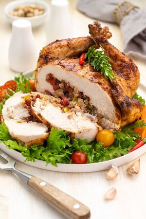 Stuffed boneless chicken garnished with fresh vegetables, lettuce, cherry tomatoes, bell peppers and fresh rosemary herbs. A large cut portion on a white dish and wooden table. Close up. Standard-Bild