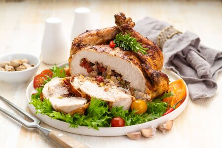 Stuffed boneless chicken garnished with fresh vegetables, lettuce, cherry tomatoes, bell peppers and fresh rosemary herbs. A large cut portion on a white dish and wooden table. Close up.