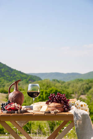 Outdoor picnics in the mountains. A picnic table set with red wine, cheese, fruits, grapes and bread stands in a meadow in green grass. The concept of secluded outdoor recreation.