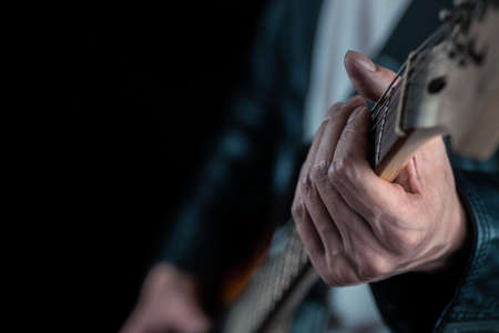 Guitarist hands and guitar strings close up. Musician man playing electric guitar. Selective focus.