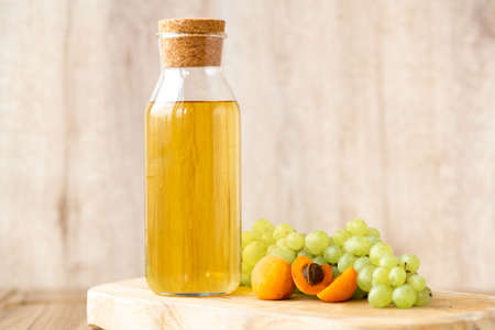 Homemade white wine or apple cider vinegar in a tall bottle with a wooden stopper. Eco-friendly food with fruits on a light wooden background. Archivio Fotografico