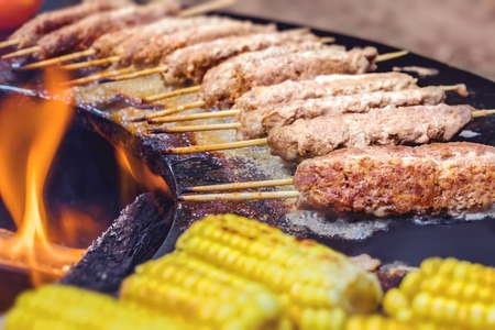 Pepper, corn, eggplant, kebabs, chicken on a street grill on an open fire. Summer food