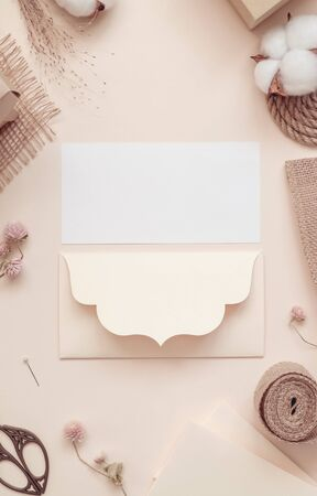 Workspace. Invitation cards, craft envelopes, cotton flower on light background. Overhead view. Flat lay top view.