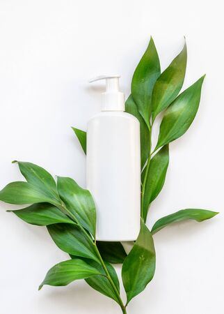 Natural organic cosmetic packaging plastic mock up with leaves. Mock-up bottle for branding and label.