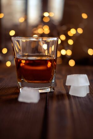 A glass of whiskey or rum with ice on a dark and bokeh Banco de Imagens