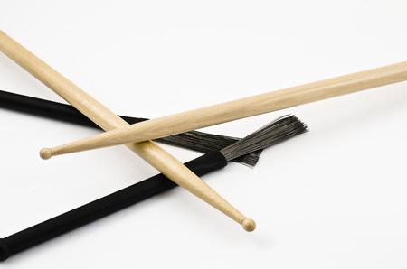 スティックと白地にドラムをプレイするブラシ