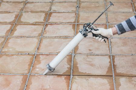 타일 바닥에 시멘트 페이스트로 밀봉 및 접착 스톡 콘텐츠