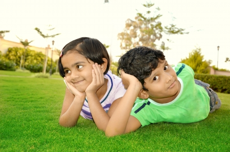 Cheerful south Asian boy and girl lying down in a lawn