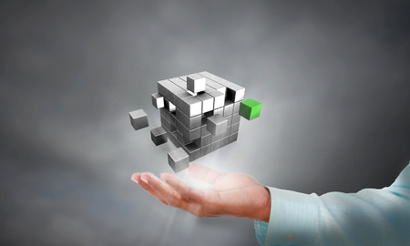 Business man holding a cube in hand, this represents holding Solution to a business problem in hand