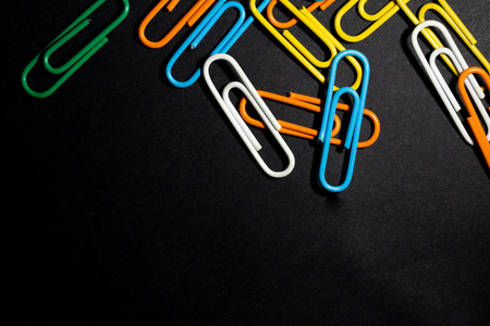 color paperclip on black background