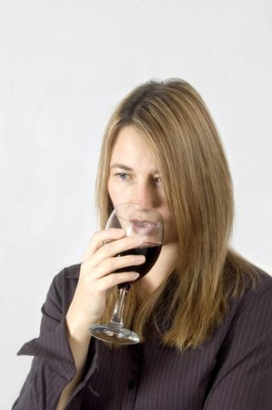 A thoughtful woman drinks a glass of red wine