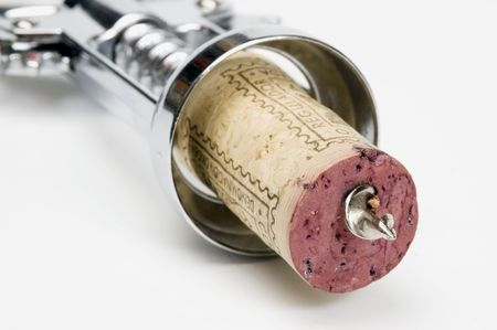 A corkscrew piercing a red wine cork on a white background