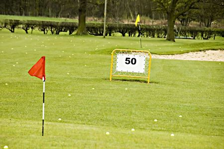 A view of a driving range with flags fluttering in the wind