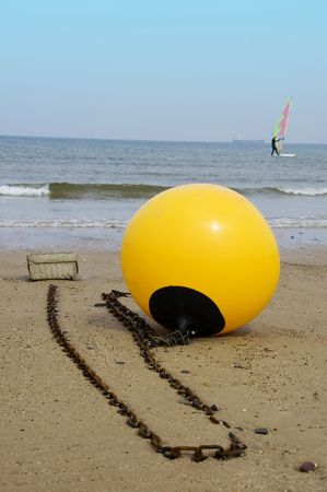 A yellow buoy sits on the beach with a windsurfer &  ship on the distant horizon