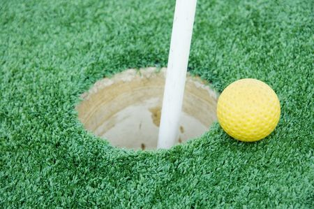 A golf ball about to roll into a hole