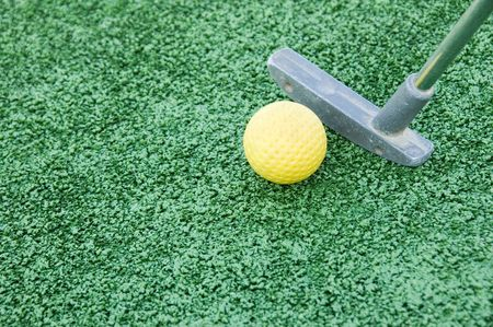 closeup of a putter and golf ball from a crazy golf course