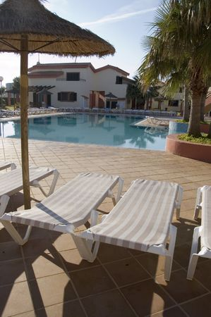 Shot of sun loungers with a pool and holiday apartment in the distance Stock Photo