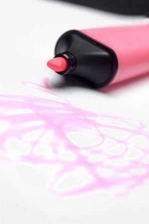 A pink highlighter pen scribbles onto paper