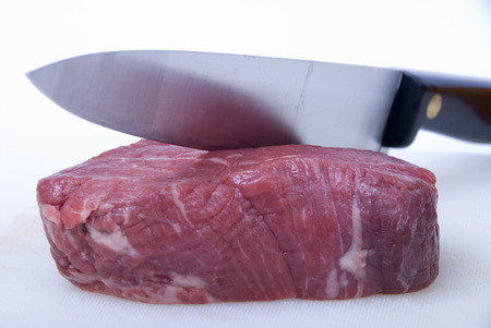 A piece of raw fillet steak about to be cut by a butchers knife