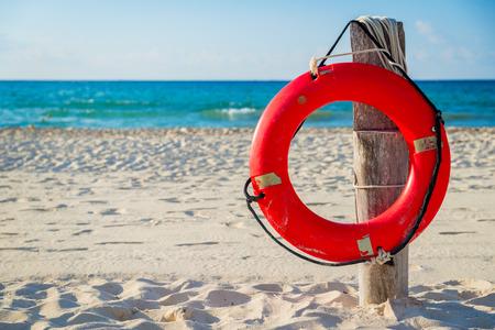 beach buoy: Life buoy on a pole on a beach in Mexico Stock Photo