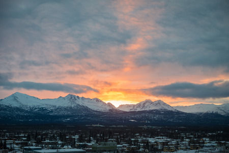 anchorage: Bright colorful sunrise behind mountains with dark snow clouds over Anchorage, Alaska Stock Photo