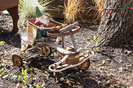 Garden gnome riding a four wheel old rusty kids bicycle with broken weel Standard-Bild