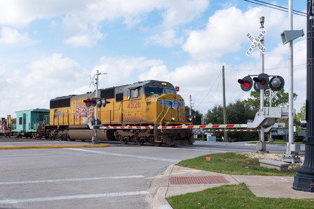 sugar land: SUGAR LAND, TEXAS - DECEMBER, 2015: Union Pacific repairs train on railroad crossing with red stop signs on December 2015 in Sugar Land, Texas Editorial