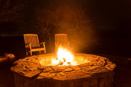 flamme incendie dans un foyer et deux chaises en bois vides à côté d'une forêt sombre à l'arrière